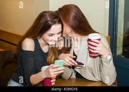 Two girls gossiping in a cafe bar - Stock Photo