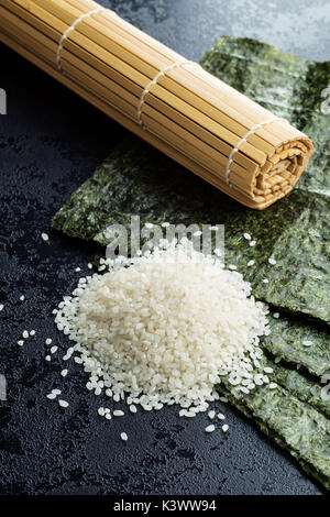 Green nori sheet , rice and bamboo mat on black table. - Stock Photo