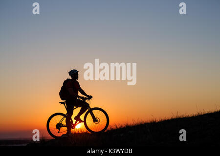 Silhouette man stand with mountain bike on the meadow - Stock Photo