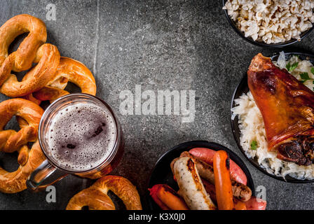 Selection of traditional German food Oktoberfest. Beer, baked pork shank, popcorn, assortment of different sausages, - Stock Photo