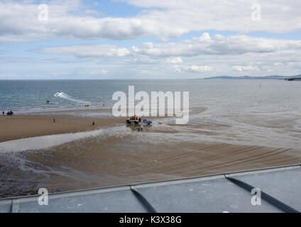 Elevated view of vehicle towing jet ski over beach to sea - Stock Photo