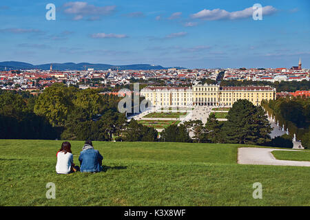 Vienna, Austria - September 24, 2014: Couple of tourists sitting on the grass with the view of Schonbrunn palace