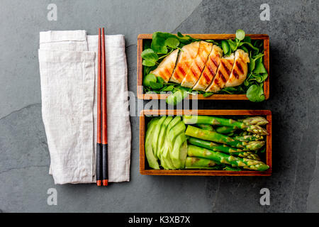 Healthy lunch in wooden japanese bento box. Balanced healthy food grilled chucken and avocado with asparagus and - Stock Photo