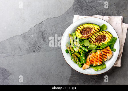 Healthy grilled chicken, grilled avocado and asparagus salad with linen seeds. Balanced lunch in bowl. Gray slate - Stock Photo