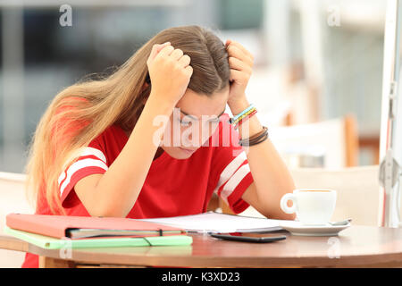 Single frustrated student girl trying to understand notes sitting in a bar - Stock Photo