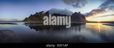 Panoramic view of Vestrahorn mountain reflected in shallow water at sunrise. - Stock Photo