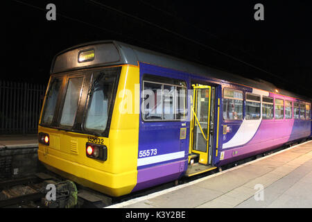 Pacer class 142 diesel multiple unit train seen at night in Lancaster railway station in bay platform number 2. - Stock Photo