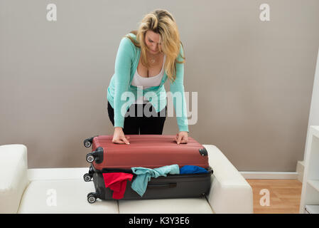 Woman Trying To Close The Overfilled Suitcase In The Room - Stock Photo