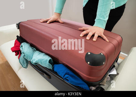 Close-up Of Woman Trying To Close Suitcase With Excess Of Clothes - Stock Photo
