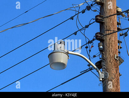 An unlit street lamp on a wood pole with telephone wires stands out against a blue sky. - Stock Photo
