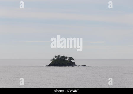 Coconut Rock in Approaches to China Strait, Papua New Guinea, South Pacific. - Stock Photo