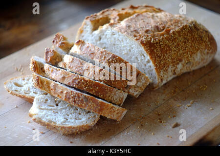 Fresh loaf of artisan bread being sliced on a wooden board. - Stock Photo