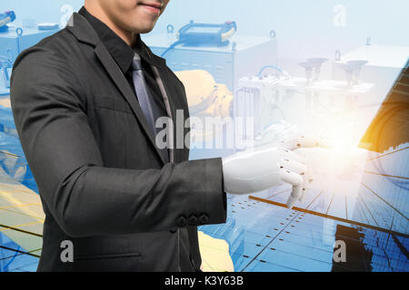 Artificial intelligence (ai) robot technology in smart factory concept. Male business suit with robotic hand point - Stock Photo