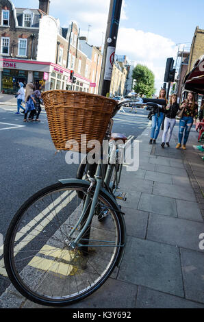 A bicycle left propped up against a lamppost in Camden, London. - Stock Photo