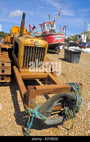 Rusty bulldozer and red fishing boat on Hastings Stade Beach, East Sussex, UK, GB - Stock Photo
