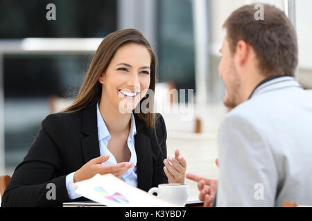 Two happy executives meeting in a restaurant and having a business conversation - Stock Photo
