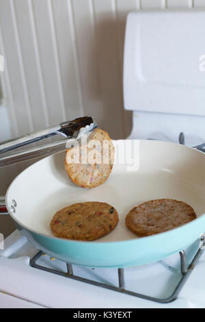 Flipping veggie burgers as they fry on the stove - Stock Photo