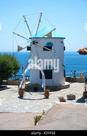 Girl taking a selfie next to traditional Greek windmill at Skinari, on the northern tip of Zakynthos - Stock Photo