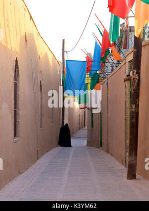 Iranian muslim woman in black chador, in the narrow streets of Yazd, Iran - Stock Photo
