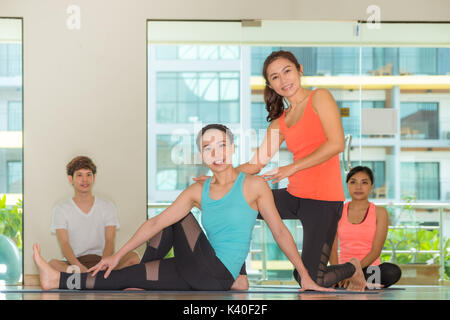 Asian woman yoga master teaching student in studio classroom,,Wellness and Healthy Lifestyle - Stock Photo