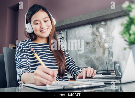 Young asian casual businesswoman listening music and writing report on office desk,work at home with online e-commerce - Stock Photo