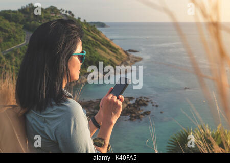 Young traveler woman use mobile phone taking of photo at beautiful of nature at top of mountain and sea view,travel - Stock Photo