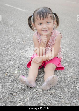 Little Asian Girl Sitting And Smiling On The Floor - Stock Photo
