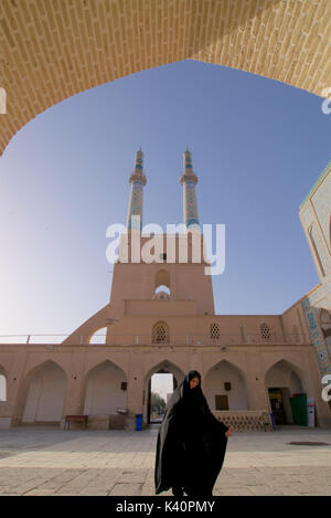 Iranian muslim woman in black chador, at Jameh Masjid. Friday Mosque, Yazd, Iran - Stock Photo