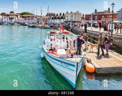 2 July 2017: Weymouth, Dorset, England, UK - Passengers with a dog boarding the pleasure boat My Girl at Weymouth - Stock Photo