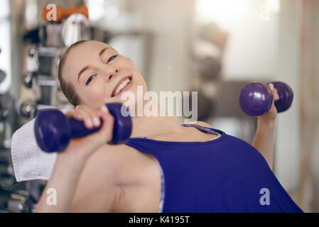 Attractive young woman working out in a gym training with a pair of dumbbells in a close up view in a health and - Stock Photo