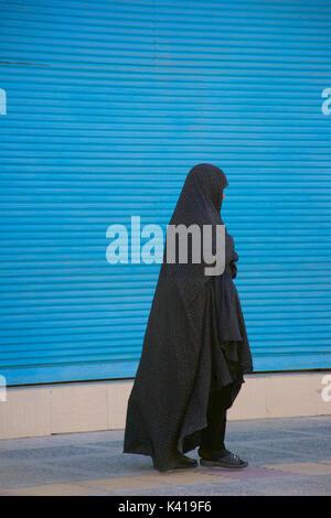 Iranian muslim woman in black chador, Yazd, Iran - Stock Photo