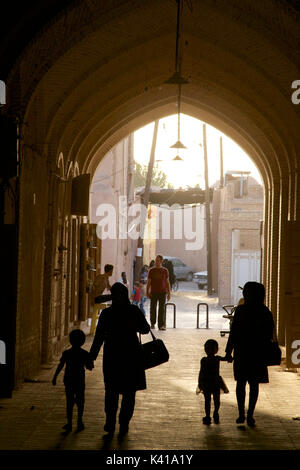 Moody late afternoon light penetrates the bazaar area, Yazd, Iran. Silhouetted Iranian family. - Stock Photo