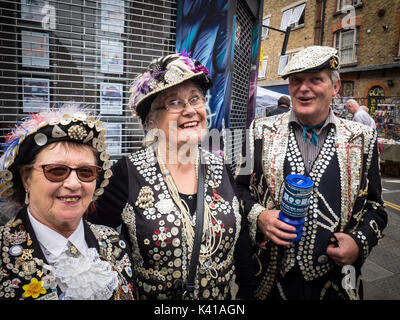 Pearly Kings and Queens collect money for Charity on Sunday mornings in London's popular Brick Lane market in Spitalfields, - Stock Photo