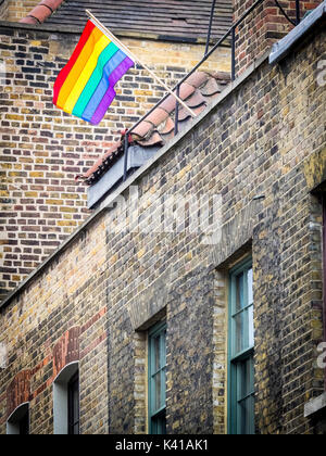 LGBT rainbow flag flies from a building in Spitalfields in London's East End. - Stock Photo