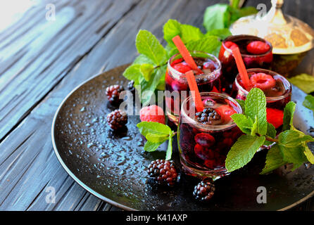 berry juice in a glass with berries, ice and mint, selective focus - Stock Photo