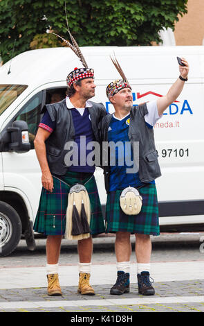 Two middle age men, Scotland football team fans in national clothes taking a selfie on the street in Vilnius, - Stock Photo