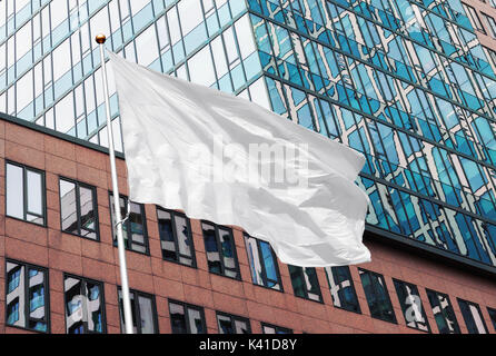 White blank flag waving in the wind in the urban background of modern buildings and skyscrapers. Perfect mockup - Stock Photo