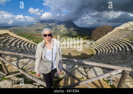 Tourist taking photo in front of greek theater of Segesta, Sicily, Italy - Stock Photo