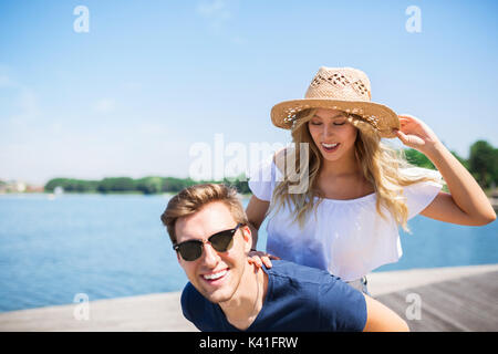 A photo of young, happy couple on holiday. The man is giving his girlfriend a piggyback. - Stock Photo