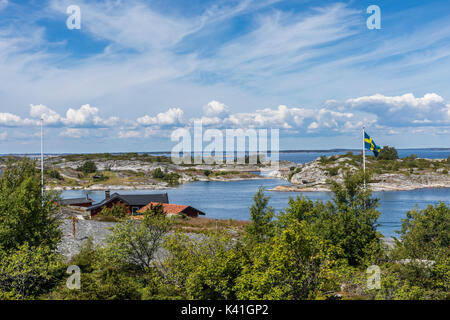 Waterfront houses on an island in the outer reaches of the Stockholm archipelago with Swedish flag - Stock Photo