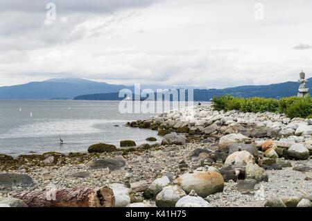 The Rocky shoreline along False Creek leading out into English Bay. - Stock Photo