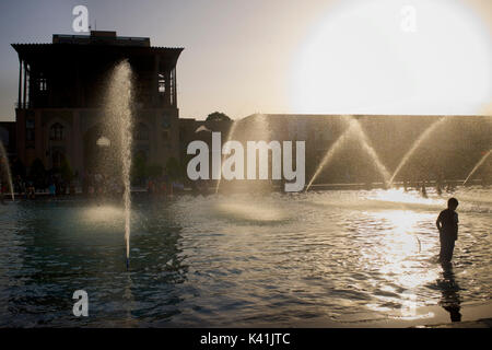 Ali Qapu Palace and public fountains in Naqsh-e Jahan Square. Imam Square, Isfahan city, Iran. Iranian boy in water. - Stock Photo