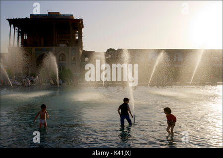 Kids playing in the public fountains in front of Ali Qapu Palace, Imam square. Naqsh-e Jahan  Isfahan city, Iran - Stock Photo