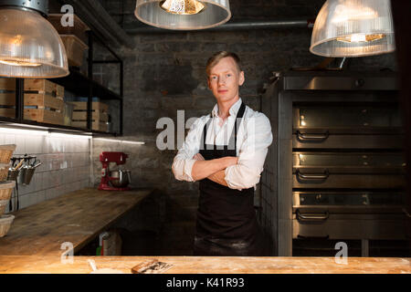 chef or baker in apron at bakery kitchen - Stock Photo