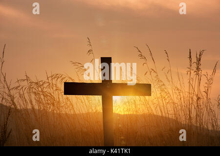 christian cross silhouette on sunset background - Stock Photo