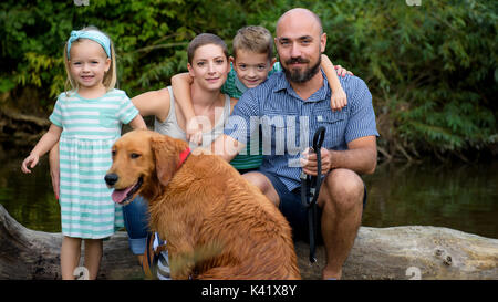 Beautiful young family with their pet dog, golden retriever, on a trip by a river - Stock Photo