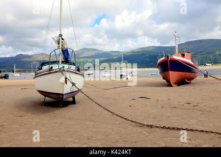 Barmouth, Wales, UK. August 05, 2017.  Boats and yachts beached at low tide in the harbor with the railway bridge - Stock Photo