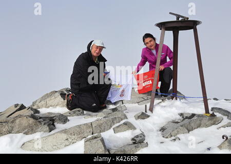 Hikers on top of Galdhopiggen the highest point of Norway and Scandinavia and Northern Europe - Stock Photo