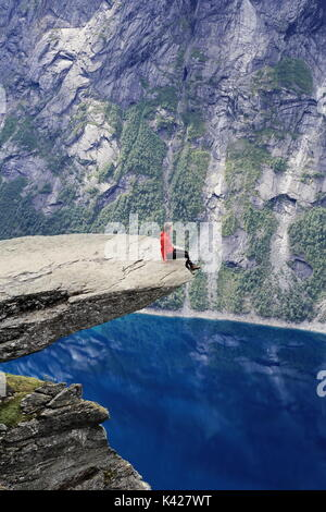 Woman Hiker enjoying view from Trolltunga rock formation in Norway - Stock Photo