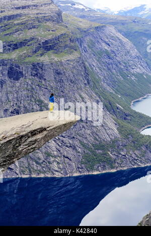 Hiker enjoying view from Trolltunga rock formation in Norway - Stock Photo